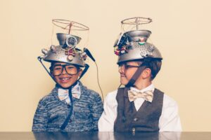 Two very young ROI solutions experts with funny hats looking at each other while laughing.